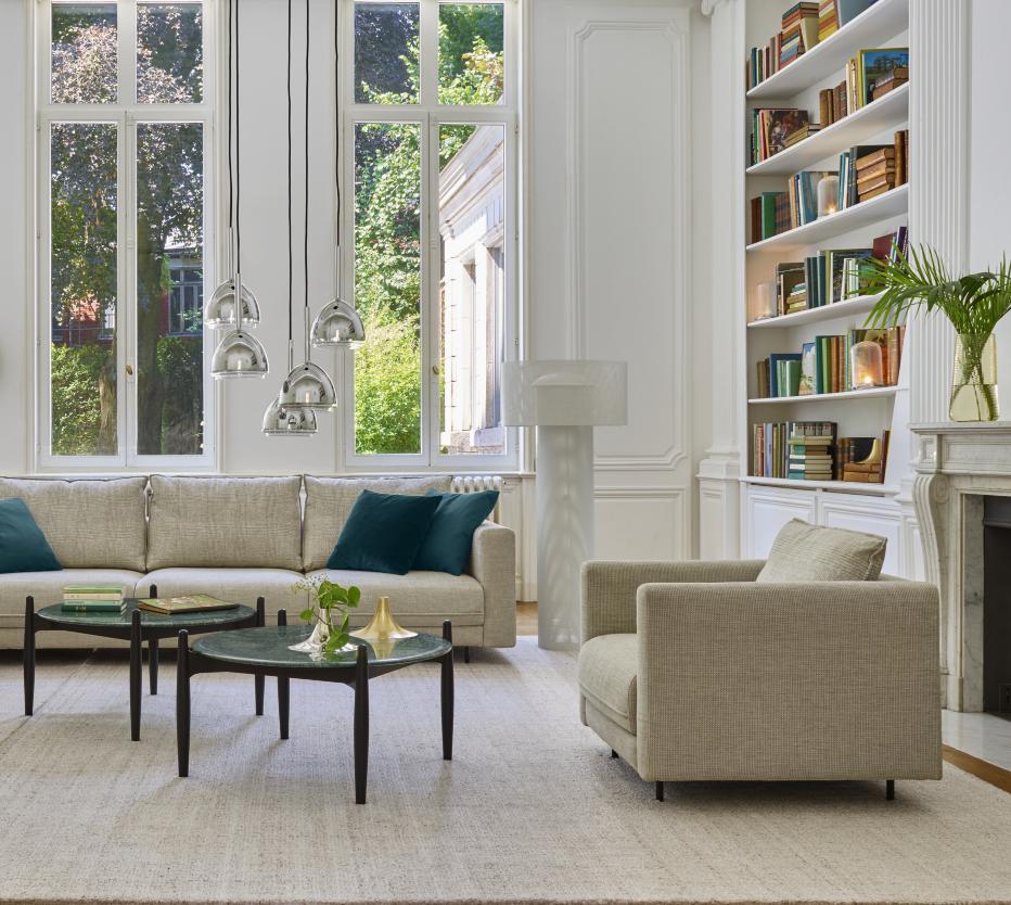 Ligne Roset Enki-sohva ja -nojatuoli, Caffè-sohvapöydät, jolla Kasckasch-vaasit. Chrome bell -riippuvalaisimet, Asola-lattiavalaisin, hyllyssä Car light -pöytävalaisin ja takan päällä saman sarjan vaasi. Mattona Fiber wood.
