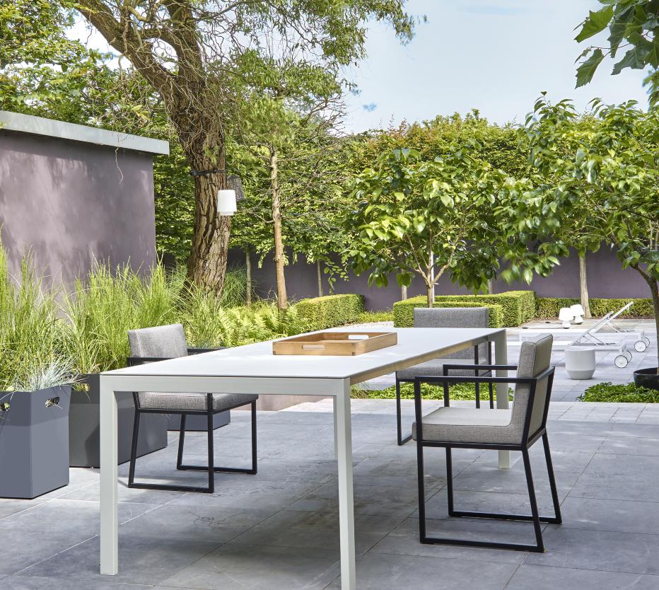 Ligne Roset ulkokalusteet terassille: Dehors-pöytä, Iso-tuolit, Azteck-tarjotin, Giardinetto-ruukunsuojat. Taustalla Lettino-aurinkotuolit ja Mushroom-valaisimet.