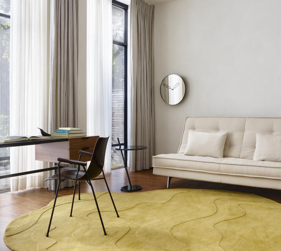Ligne Roset Nomade Express -vuodesohva, Good Evening -sivuppöytä, Tanis-pöytä, jolla on Pájaros-koristelintu, lattialla Gavrinis 3 -matto, seinällä Mirror Clock -kello ja tuolina CM131